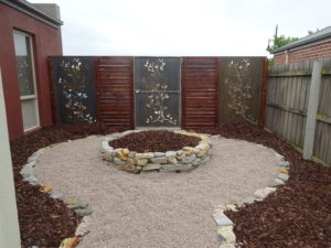 Low maintenance feature area with rock, mulch and corten screens